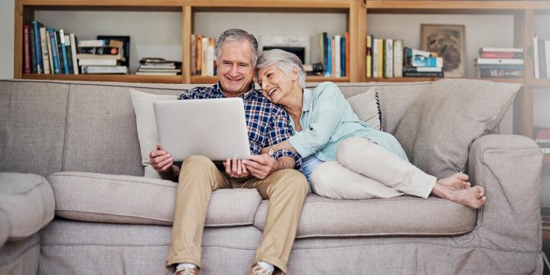 happy couple looks at laptop on couch